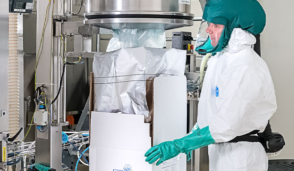 CordenPharma Sterile Segregated Antibiotic APIs technician in full PPE packaging sterile API near cGMP-compliant equipment