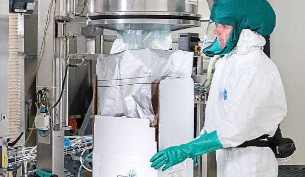 CordenPharma Sterile Segregated Antibiotic APIs technician in full PPE packaging sterile API near cGMP-compliant equipment