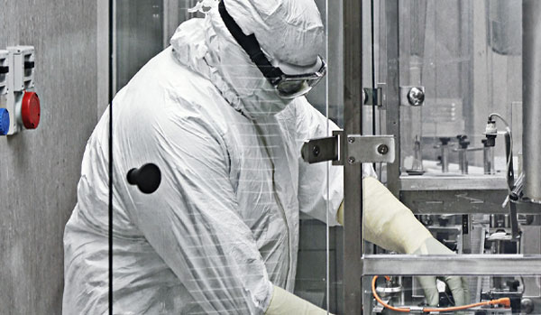 CordenPharma Sterile Powder Fill Injectable Formulation Drug Products operator at Latina site in full PPE operating cGMP production equipment