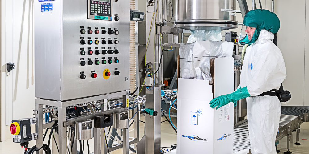 CordenPharma Antibiotics Technology Platform operator in full PPE packaging and reviewing cGMP-compliant equipment