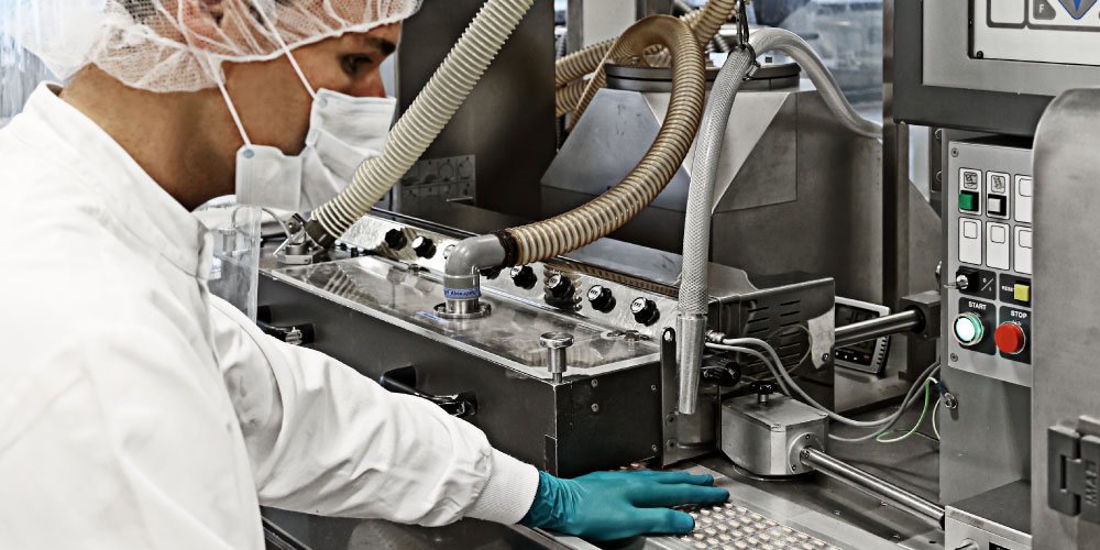 CordenPharma Highly Potent & Oncology Technology Platform technician in full PPE monitoring encapsulation equipment
