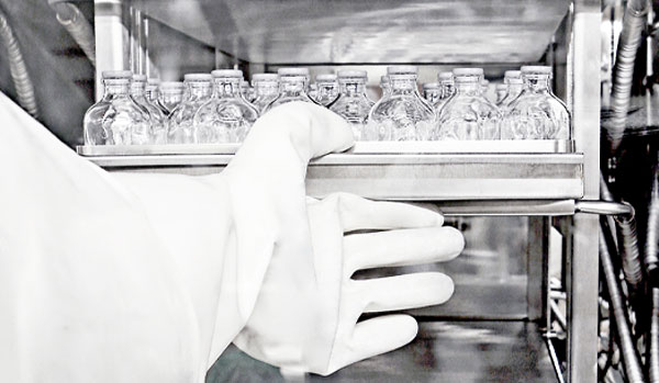 CordenPharma Sterile Powder Lyophilized Vials Injectable Formulation Drug Products scientist in full PPE close-up with rack of vials in cGMP production equipment