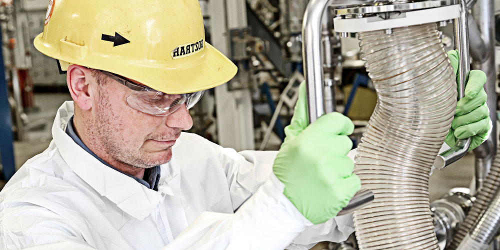 CordenPharma Peptides, Lipids & Carbohydrates Technology Platform - hard-hatted operator using API processing equipment