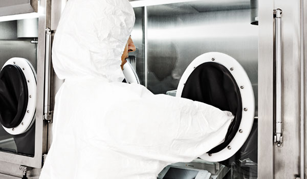 Corden Pharma Latina S.p.A. scientist works at glove box for sterile liquids & powder lyo injectable formulation drugs.