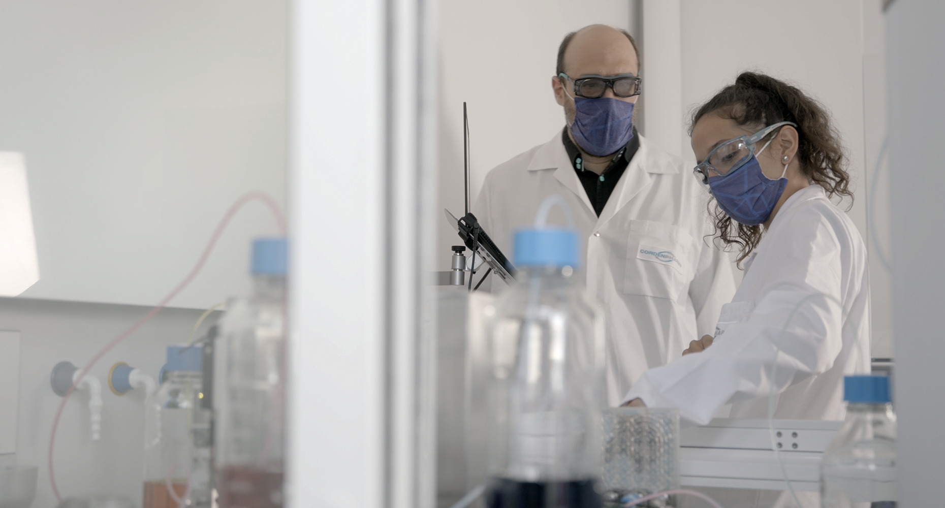 Two lab technicians in continuous manufacturing flow chemistry lab at CordenPharma Chenôve, France